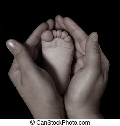 close-up of womans hands holding infants foot - close-up of...