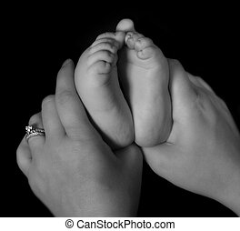 close-up of mother hands holding infants feet in black and...