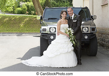 wedding - beautiful bride and groom in front of a big car