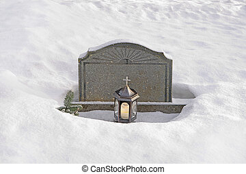 tombstone in snow - Granite tombstone with candle in winter