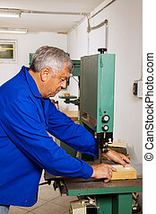 Carpenter on a band saw - An elderly carpenter on a band saw...