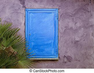 Blue wood shutter on purple wall