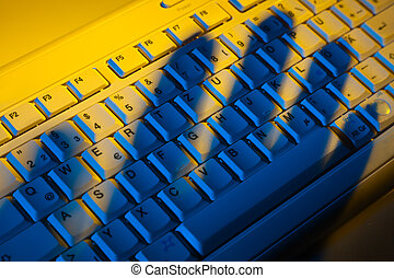 Keyboard and shadow. Data theft. - Computer keyboard and the...