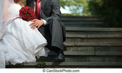 bride and groom sit on the stairs