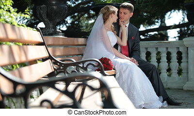bride and groom on the bench - bride and groom sit on a...