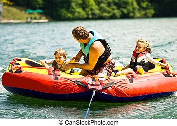 Family Fun Tubing on a Lake - A man and his children riding...
