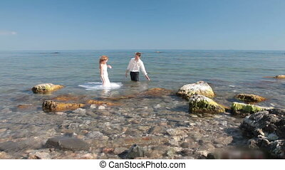 bride and groom splashes in  water