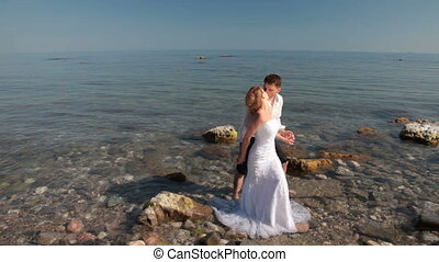 bride and groom kissing near sea