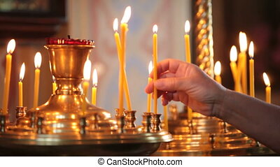 hand with candle in church - hand with a lit candle in the...