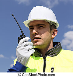 portrait of builder with transmitter in building site