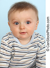 Surprize baby - Surprized looking baby boy against a blue...