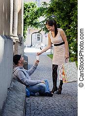 Woman gives a beggar money