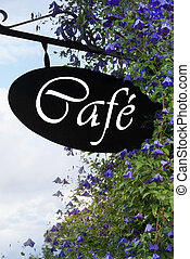 Cafe sign with blue or purple flowers