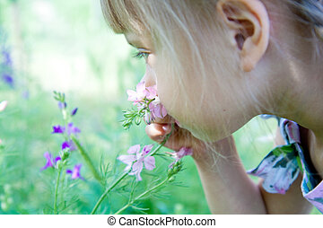 little girl is smelling the blooming flowers. - A little...