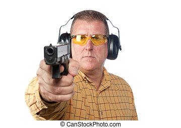 Man shooting gun - A man aims a handgun while wearing proper...