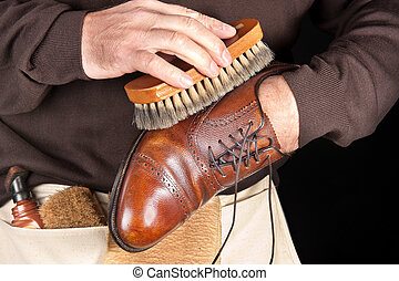 Shoe polisher - A shoe shiner works on the final buffing of...