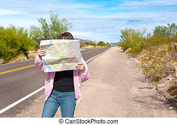 Woman reading road map - A woman stands along side a remote...