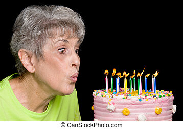Adult blowing out candles - A senior female blows out...