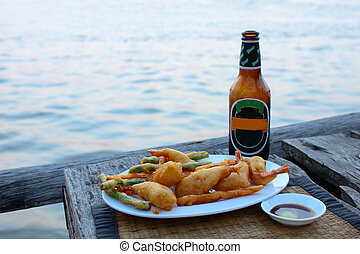 Prawn tempura with cool beer and river background