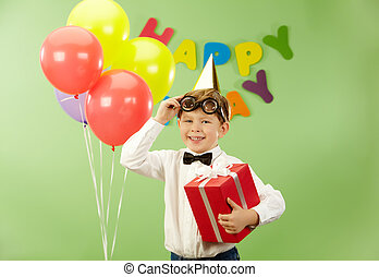 Birthday mood - Portrait of happy lad with giftbox putting...