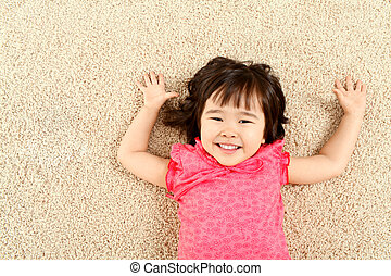 Laughter - Portrait of cute child laughing while lying on...
