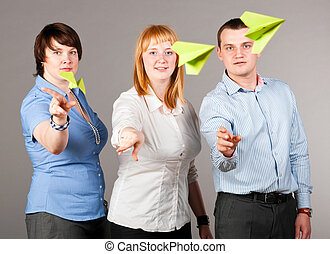 throwing paper planes - three business people are throwing...