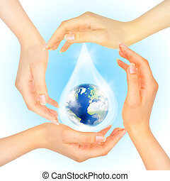 Drop of water with Earth inside and hands on white . The...