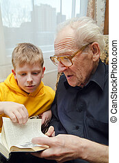 Reading Book Together - grandfather reading book aloud to...
