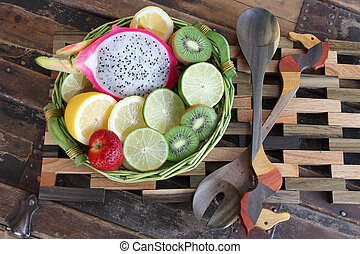 Fruit basket on wooden placemat with ornate spoons