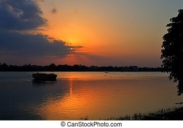 Sunset, boat heading towards horizon, golden rays, river...