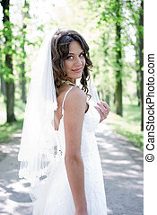 young bride standing in an alley in the park