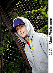 Young man wearing a hoodie - Young man with a blue hat and a...