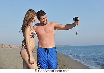 happy young couple in love taking photos on beach - happy...