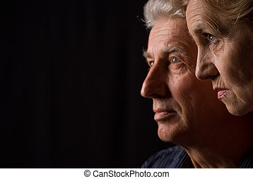 aged people on a black - portrait of a two people looking at...