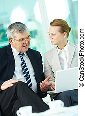 At meeting - Portrait of boss and employee working with...