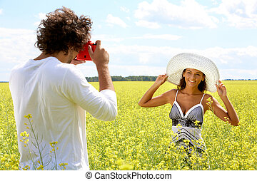 Posing - Image of young guy taking photos of pretty girl on...