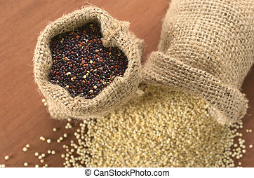 Raw red quinoa grains in jute sack on wood, with white quinoa lying beneath. Quinoa is grown in the Andes and is valued for its high protein content and nutritional value (Selective Focus, Focus on th