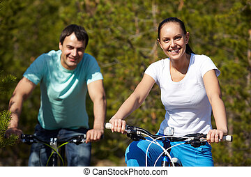Cycling couple - Portrait of two young people on bicycles