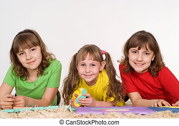three girls playing on the carpet on a white background