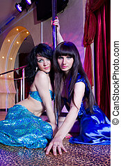 Two strippers posing on stage at the pole