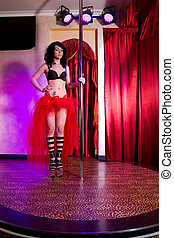 Stripper chick posing on stage at the pole