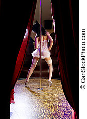 Stripper girl pole dancing in nurse costume - Young...