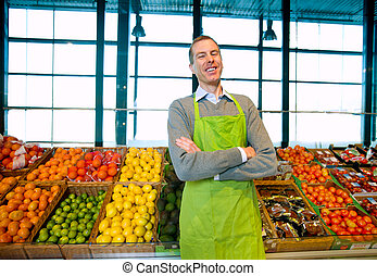 Grocery Store Owner - A grocery store owner standing in...