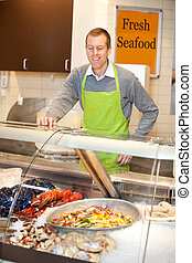 Fresh Seafood - Market assistant looking at fresh cold...