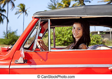 Female teen driving convertible car
