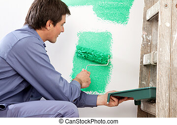 Mature man painting the wall with a roller while holding a...
