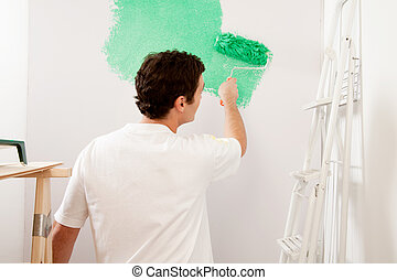 Faceless Painter - A faceless male painting a wall with a...