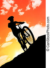 bikecyclist - silhouette of a cyclist against the sunset in...
