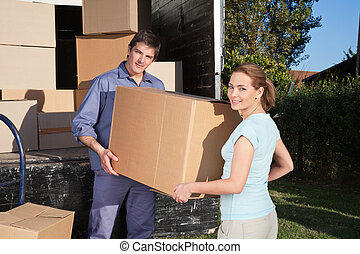 Portrait of couple carrying cardboard box while moving into...