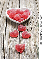 Red heart shaped jelly sweets on wood